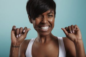 woman smiling flossing keeping up with dental hygiene through the quarantine