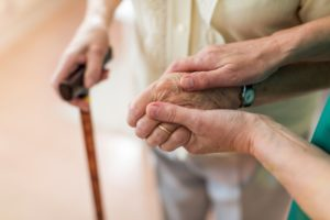 caretaker's hands holding senior's hands