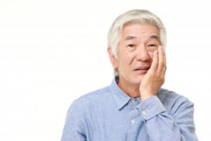 man holding his face needing to remove a failed dental implant
