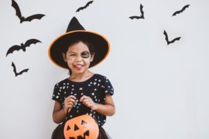 child wearing a costume who knows about cavity prevention during Halloween